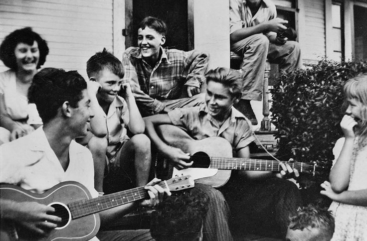 George Jones playing guitar as a young boy on porch in Beaumont, Texas
